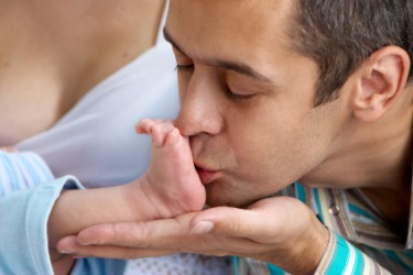 A father kisses his babys foot in an act of endearment.