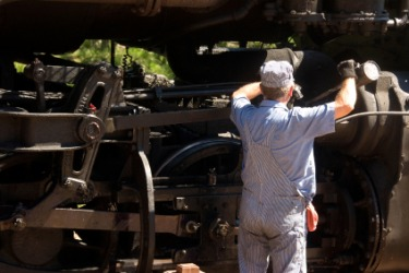 A railroad engineer working in his locomotive.