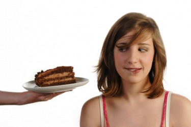 Someone trying to entice this woman with a piece of cake.