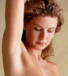 Woman with arm raised revealing armpit.