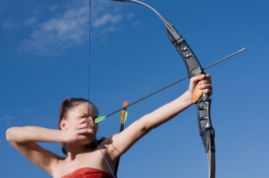 A woman about to shoot an arrow from a bow.