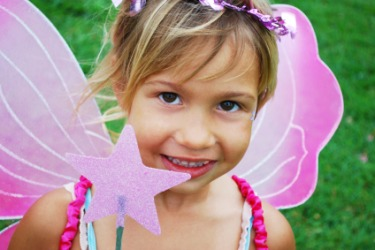 A little girl dressed as a fairy.