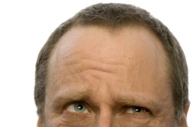 A man wrinkling his forehead.