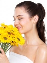 A woman enjoys the fragrance of her flowers.
