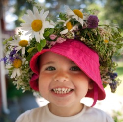 A child with a garland of flowers on her hat.