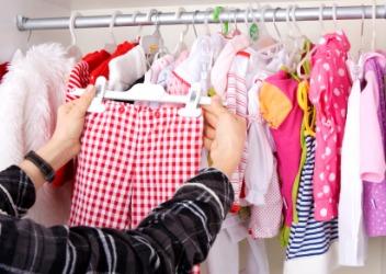 A woman choosing a garment for a child.