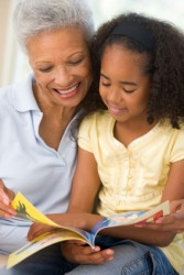 A grandmother reads to her granddaughter.