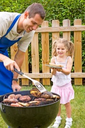 A man cooks food on a grill for his daughter.
