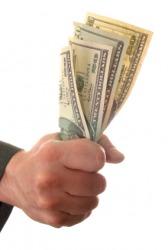 A hand grips money.