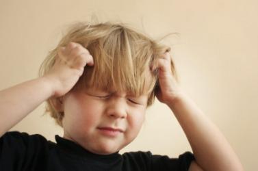 A little boy holding his head.