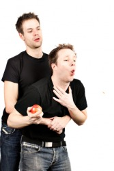 A man administers the Heimlich maneuver to another.