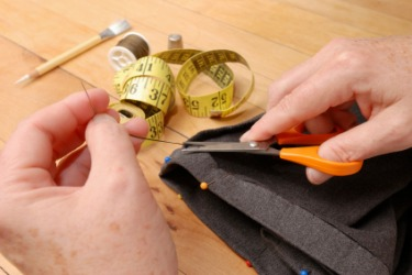 A woman puts a hem on a garment.