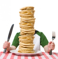 This mans face is hidden by a stack of pancakes.