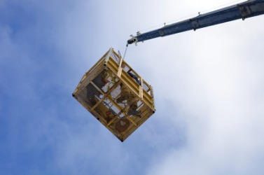 A crane is used to hoist a basket in the air.