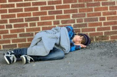 A homeless man asleep on the street.