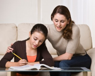 A woman helps her daughter with her homework.