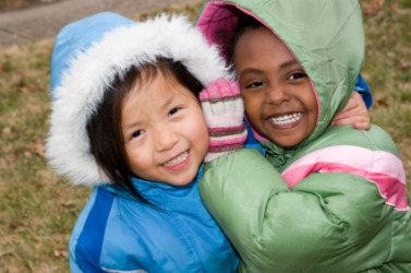 Two children with hoods on their coats.