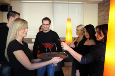 A hostess serving drinks to her guests.