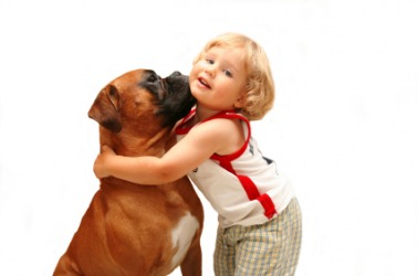 A little girl gives her dog a hug.