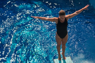 A diver about to immerse herself in water.