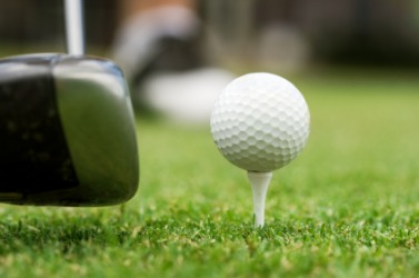 A golf club about to impact the ball.