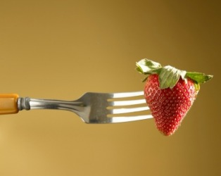A strawberry impaled by a fork.