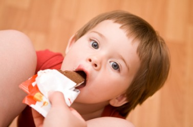 A child receives a treat from an indulgent parent.