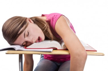 A girl lies inert on her desk.