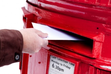 A man inserts a letter in to a postbox.