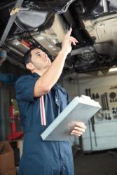 A mechanic inspects an automobile.
