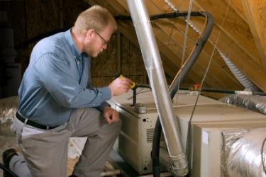 A service man performs an inspection of a furnace.