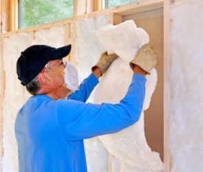 A man insulates a building.