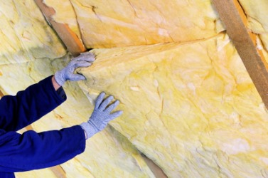 A man installs insulation in a building.