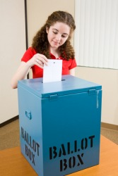 A young woman placing her ballot into a ballot box.