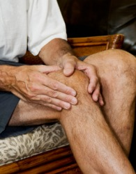 A man massaging his knee joint.