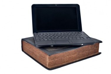 A laptop computer juxtaposed over a book.