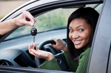 A woman receives the key to the car.