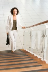A woman climbing stairs holding onto the banister.