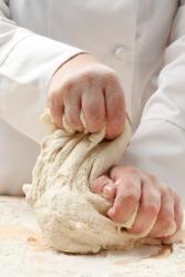 A baker kneading dough.