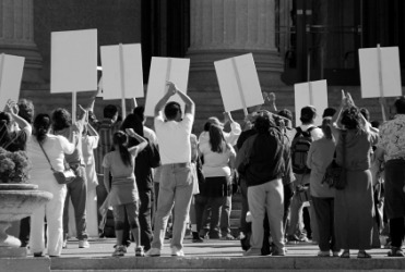 A group of people hold up protest signs.