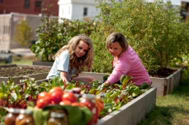 A mother and daughter tend a garden.