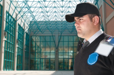 A security guard stands as sentinel in front of an office building.