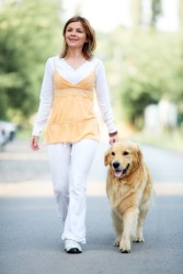 A woman takes her dog for a stroll.