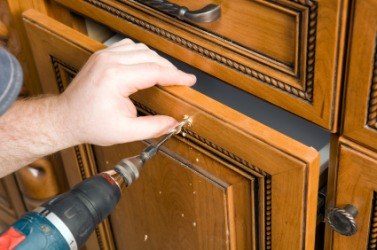 A person bores a hole in a cabinet door.