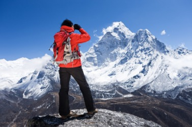 A hiker views a snow covered mountain range.