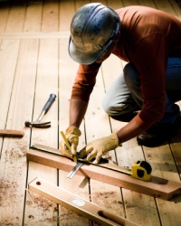 A man measures lumber for a deck.