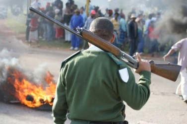 A guard faces a group of rioters.