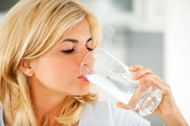 A woman swallows a glass of water.