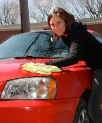 A woman applying wax to her car.
