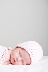 A newborn wearing a nightcap.